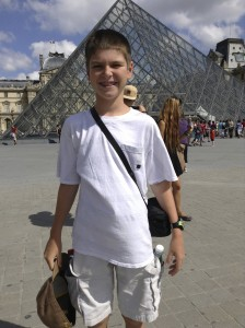 """Thing 1 at the famous """"pyramid"""" entrance to the Louvre."""