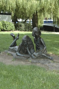 Alice and her sister, reading, as depicted in Alice in Wonderland, the novel by Lewis Carroll.